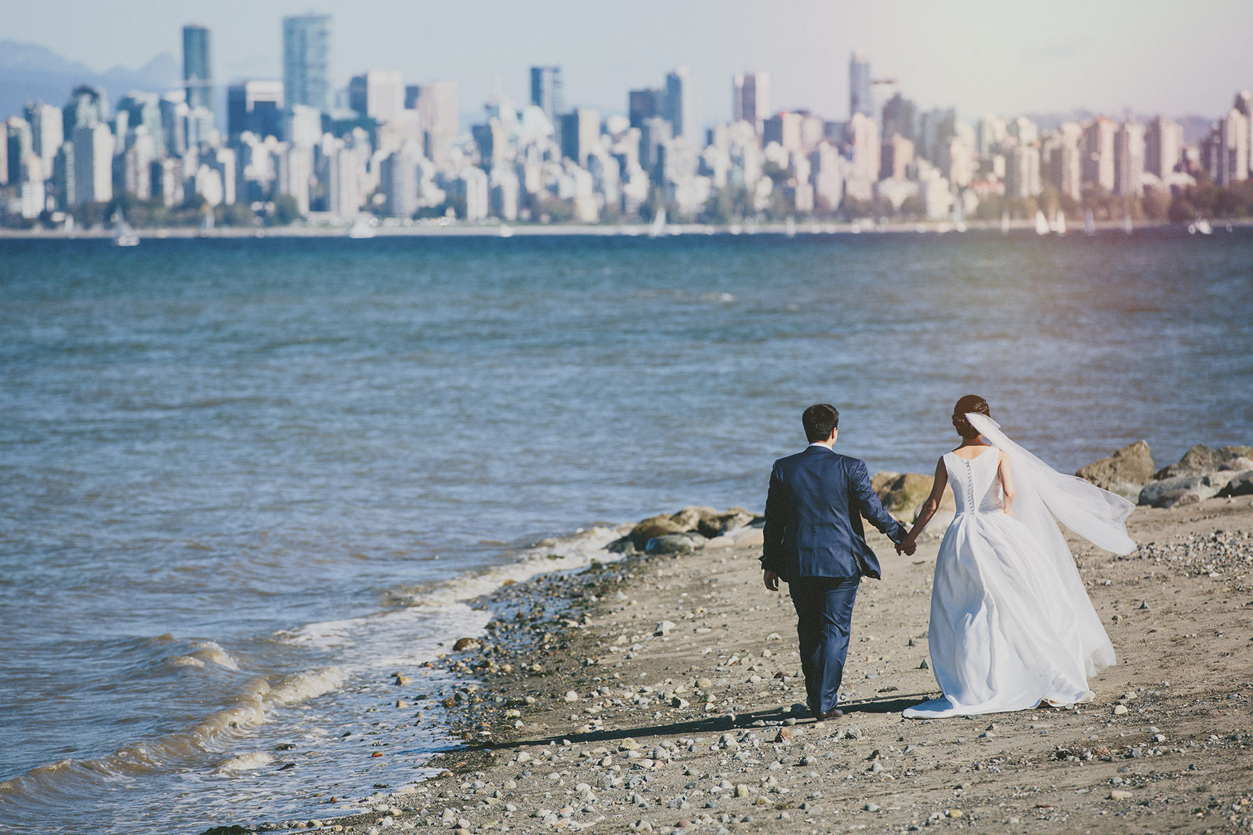 a bride and groom stroll Jericho beach with a view of downtown vancouver before them www.lucida-photography.com