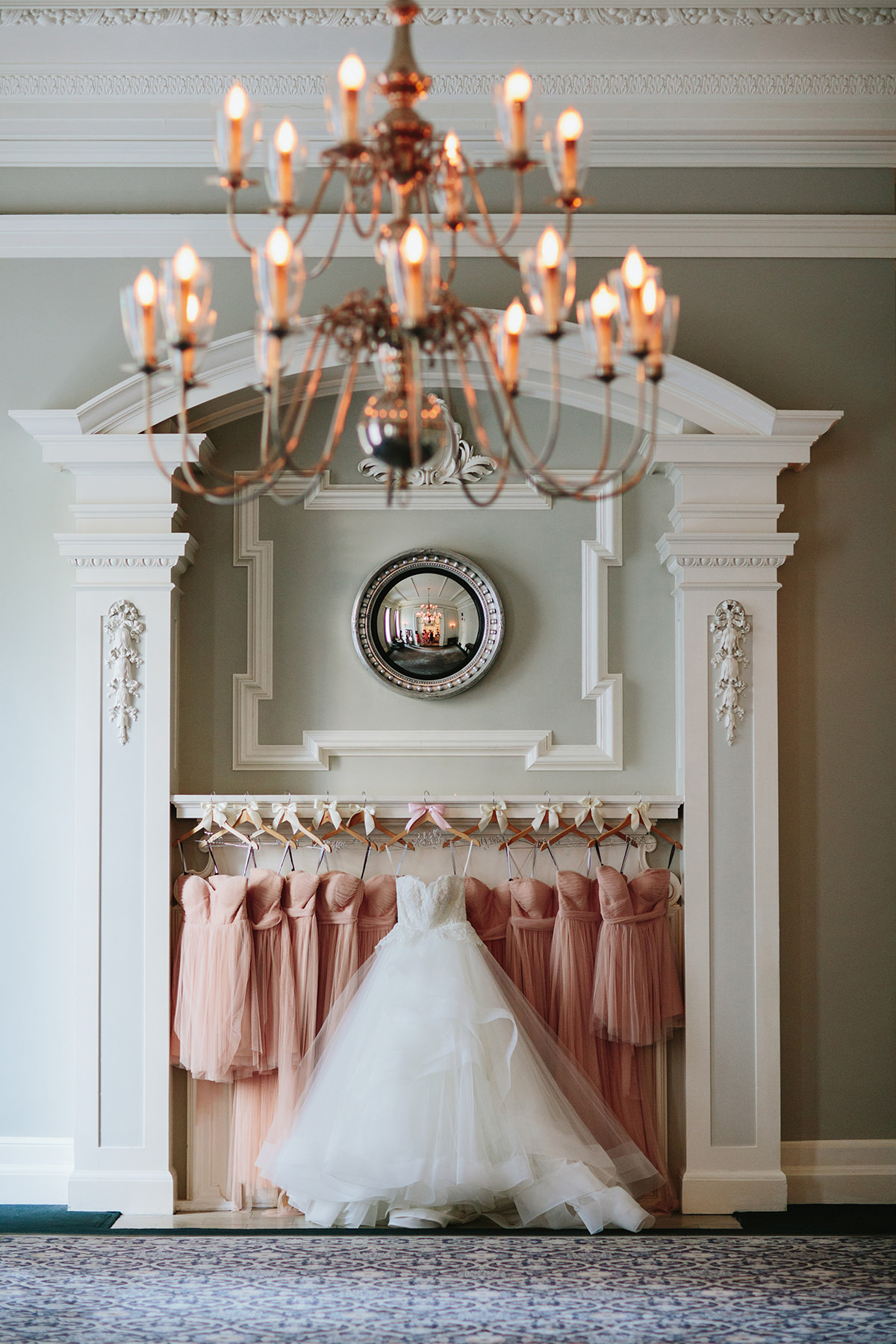 wedding dress and bridesmaids dresses hang on the fireplace mantle of the georgian room of the vancouver club www.lucida-photography.com